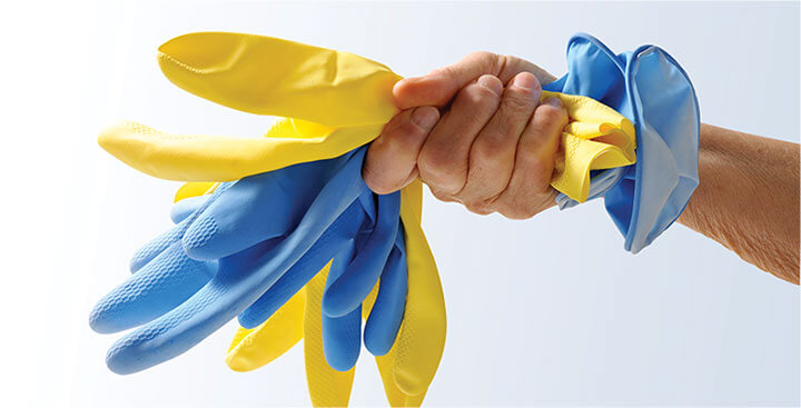 photo of a cleaner holding a stack of plastex gloves