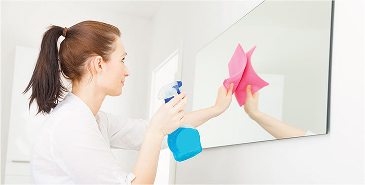 photo of a cleaner wiping a mirror