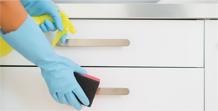 photo of a cleaner cleaning a kitchen counter with blue plastex gloves on